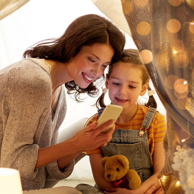 Mother and daughter on smartphone in heated home using power